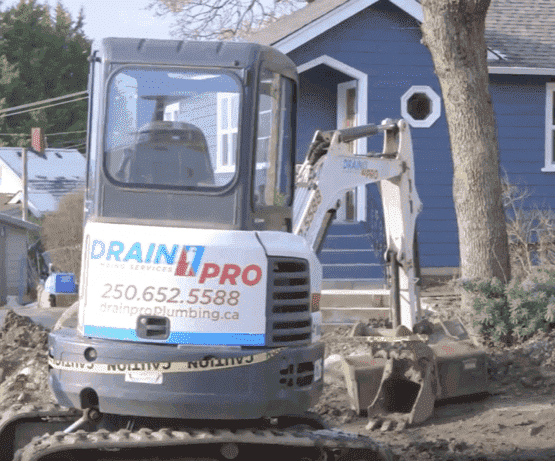 Drain Pro excavation equipment in the yard of a house getting drain line excavation service.