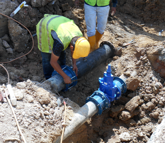 two plumbers installing a drain line in an excavated hole.