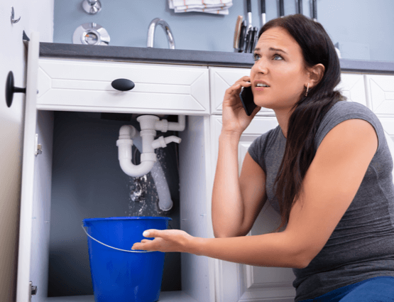 Woman on the phone with a plumber after putting a bucket under a leaking drain pipe.