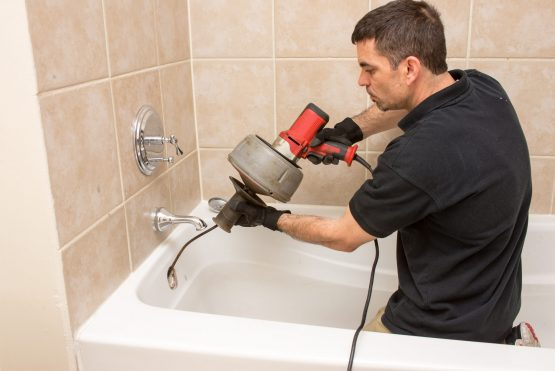plumber using a power tool to fix a clogged train in a bath tub.