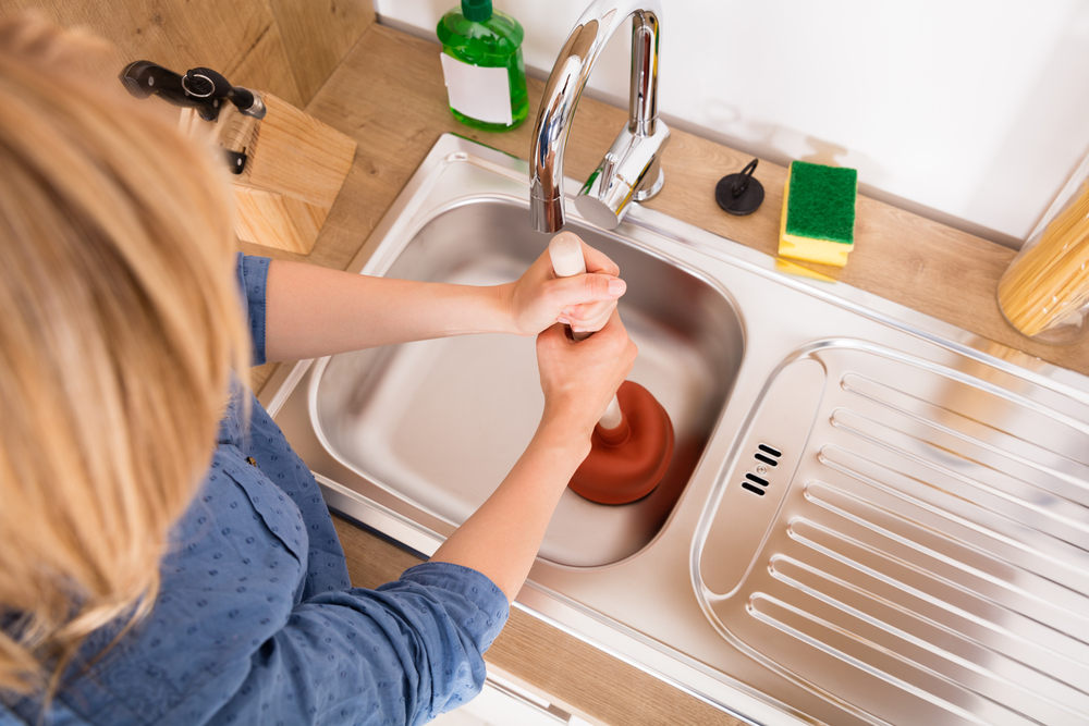 woman using a plunger to clear a clogged kitchen sink drain.
