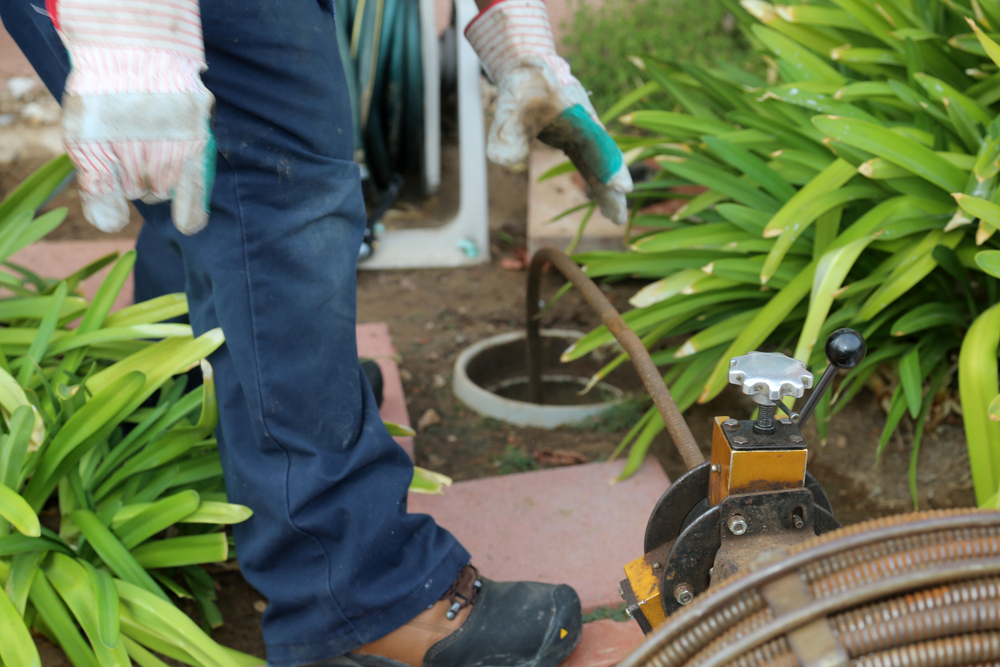 worker inspects sewer line issues