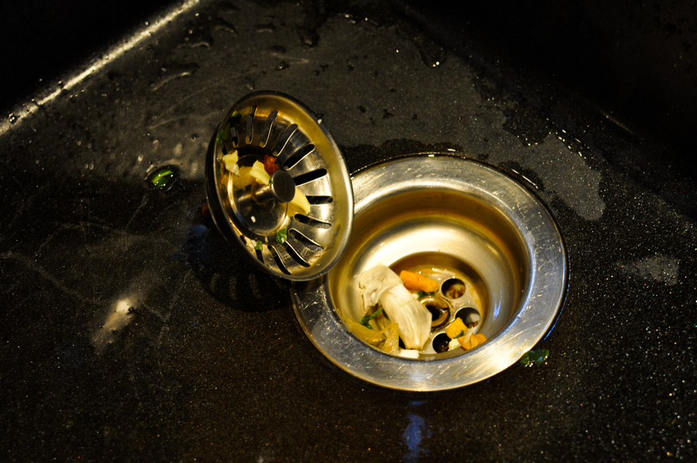 kitchen sink with food scrapes that will cause a clogged pipe