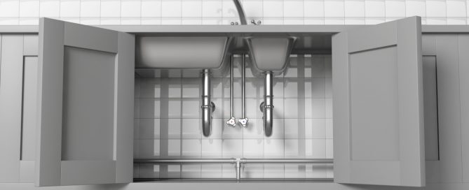 kitchen sink cabinets open with visible pipes