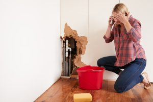 woman calling plumber for help with pipe burst and wall damage