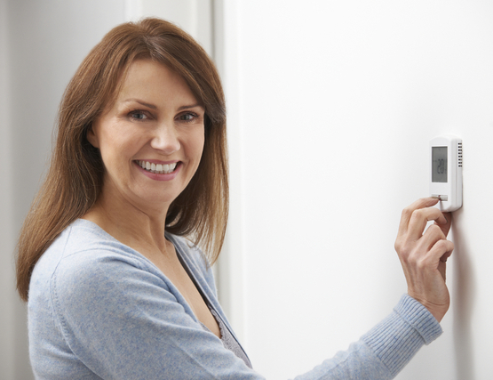 a woman standing by the wall that has a thermostat system to control her home's heating system